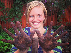 Happy young woman farmer with dirty hands