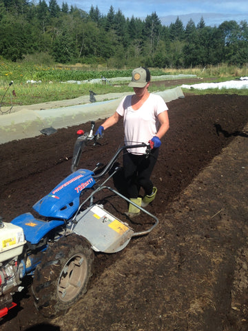 Person Tilling the field with equipment at Shelter Farm Port Alberni Shelter Society