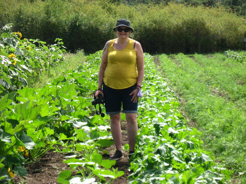 Person standing in garden with camera at the Farmland Trust Society (Greater Victoria)