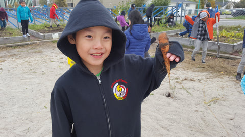 Kid holding freshly picked carrot grown at school in Northwest Territories - Food First Foundation.