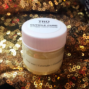 A jar of Tru – Cuticle Cure is sitting on top of a gold glittery fabric. The label on the jar lists its ingredients: Beeswax, lavender, and geranium.
