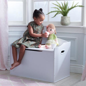 Girl sitting on white Toy Box with her doll