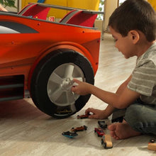 Boy playing with rotating tire - hidden car compartments of Speedway Play and Store Activity Table