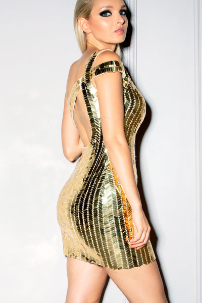 Model posing in our Alexandra gold sequin dress showing the three quarter back view.