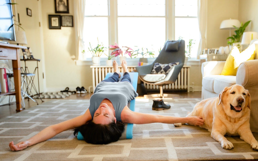 Woman laying back on Lull, our gentle inversion wellness furniture piece.