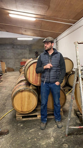 PROFILE PICTURE NATURAL WINEMAKER ROMAIN LE BARS SOUTH OF FRANCE IN FRONT OF BARRELS WITH TASTING GLASS