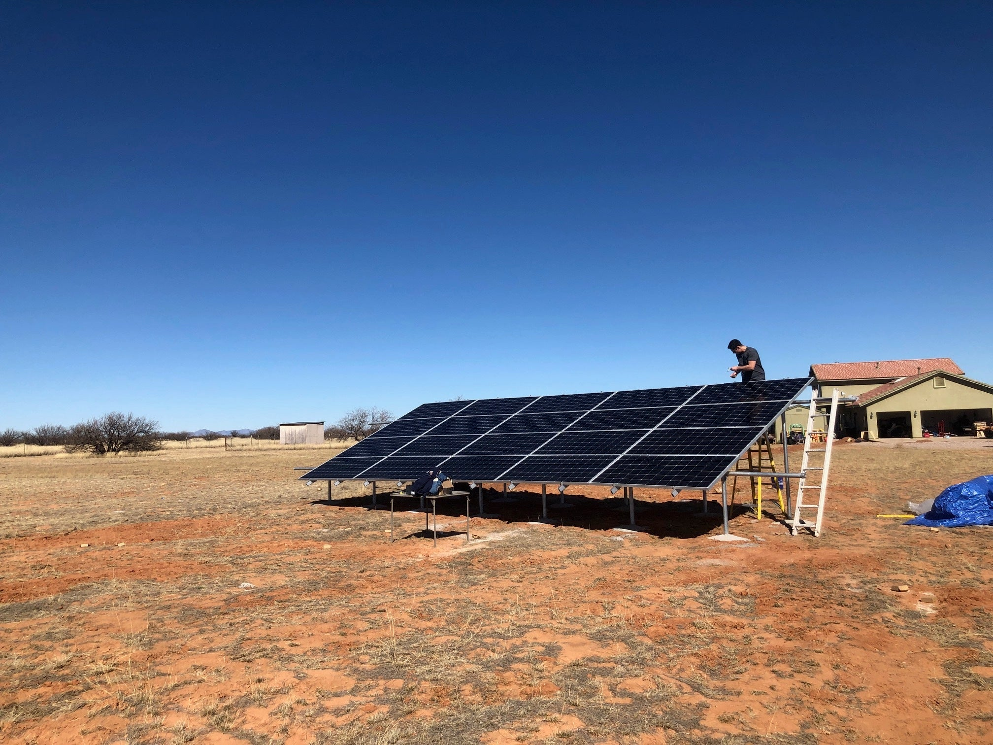 man installation solar panels on a ground mounted system