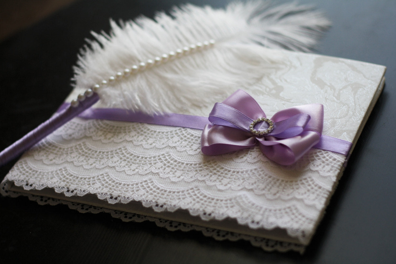 purple white signin book and ostrich feather violet pen wedding