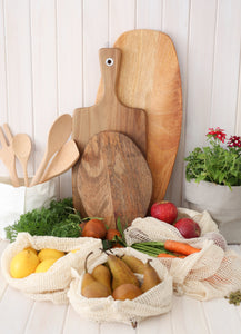 Reusable fruit and vegetable bags sitting on kitchen bench with fresh produce