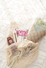 Cotton net tote bg with magazine and flowers on a bed