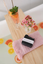 activated characoal and grapefruit soap bar sitting on a wooden bench in the bathtub