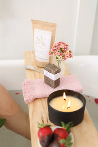 wooden bath shelf with candle, soap bar and tea