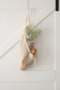 Cotton net string bag hanging from white farmhouse door