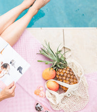 Lady sitting by the pool with a magazine and sunglasses and cotton net tote bag with pineapples and oranges.