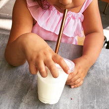 Child drinking a milkshake with a reusable straw.