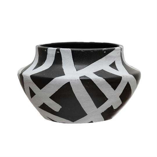 Round terracotta pot in black with white abstract designs.