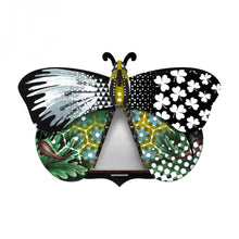 Aida butterfly wall cabinet wings open with mirror inside, with collage of patterns in green, black, and blue