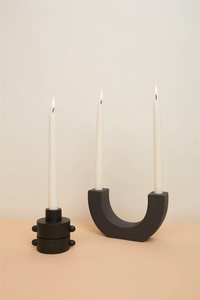 black u-shape ceramic double taper holder with 2 lit candles next to 2 black round single taper holder with lit candle