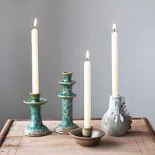 collection of candle holders with lit candles on wooden table