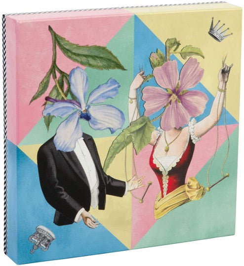 Christian Lacroix puzzle, whimsical illustrated art depicting male & female figures with floral faces. Pastel colored triangles in background.