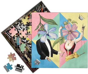 Christian Lacroix puzzle, whimsical illustrated art depicting male & female figures with floral faces. Pastel colored triangles in background. Pieces of puzzle in background.