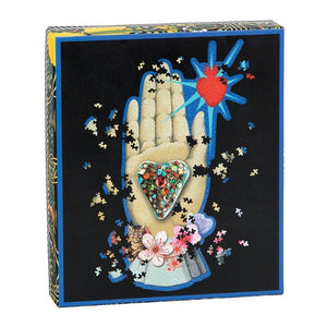 Christian Lacroix puzzle, whimsical illustrated art depicting a hand palm, heart, floral, and heart.