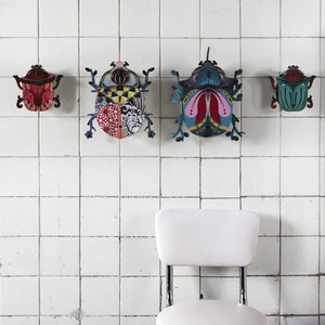 Collection of medium and large beetle wall cabinets on white tiled wall with white chair underneath