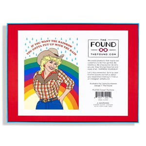 "Dolly Parton puzzle in cowgirl outfit with rainbow and raindrops in background and text above in red that reads ""If you want the rainbow, you gotta put up with the rain"" back of box"