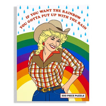 "Dolly Parton puzzle in cowgirl outfit with rainbow and raindrops in background and text above in red that reads ""If you want the rainbow, you gotta put up with the rain"" Front of box"