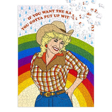 "Dolly Parton puzzle in cowgirl outfit with rainbow and raindrops in background and text above in red that reads ""If you want the rainbow, you gotta put up with the rain"""