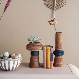 terracotta striped bowl with rattan rim and abstact vases with books and dried succulents