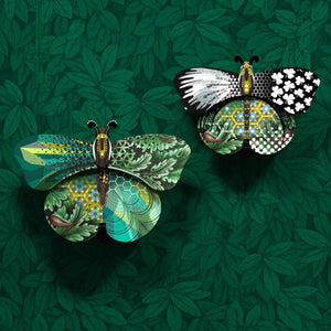 Magda and Aida butterfly wall cabinets with a collage of green, blue, and black patterns on green leaf wallpaper