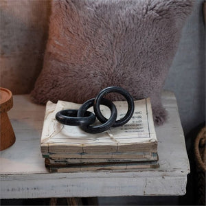 Marble chain black, 3 links on stack of old books, fur pillow on background on distressed white table