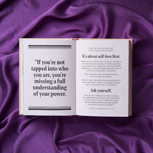 Open book with black and white text on top of purple fabric.