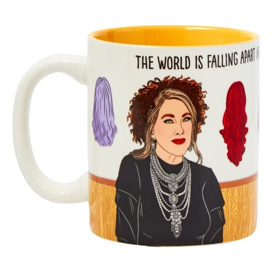 Moira Rose illustration mug with wigs on background. Text across the top that reads, The World Is Falling Apart.  Yellow color inside mug.