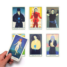 Assorted movie tarot cards with hand holding 1 card