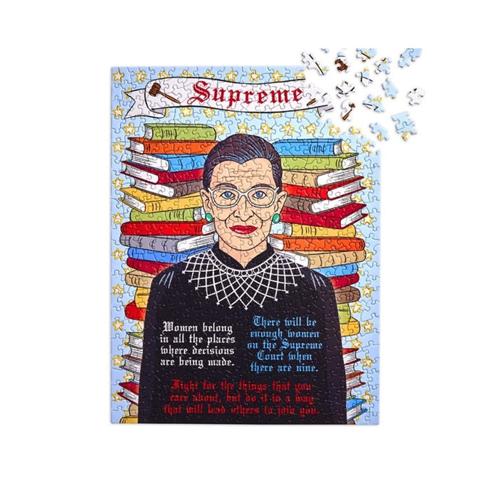 500 piece puzzle of Ruth Bader Ginsburg in front of stack of books with some of her famous quotes. Banner on top that says Supreme and 2 gavels on either side