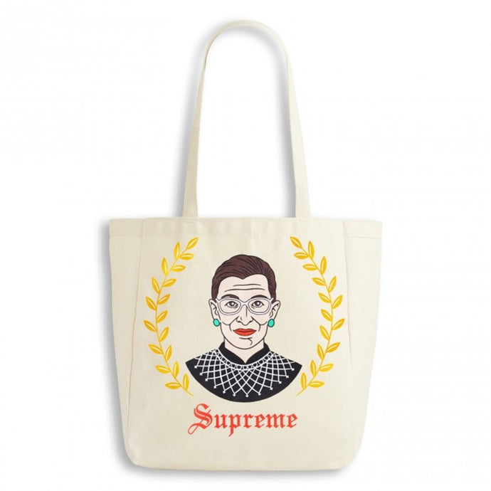 Ruth Bader Ginsburg natural tote bag with yellow leaves on either side.  Supreme text in red old english font.