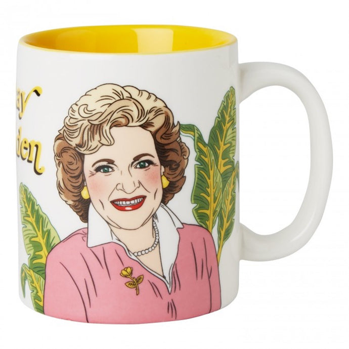 White ceramic mug with Betty White illustration, palm leaves in background with Stay Golden text in yellow. Inside mug is solid yellow.