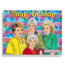 Golden Girls puzzle, multi-color palm leaves in background with Stay Golden text on top. 500 piece puzzle