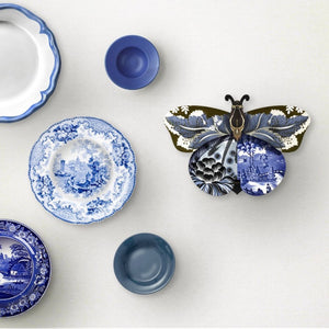 Tosca butterfly wall cabinet on mounted on white white wall with a variety of blue and white plates