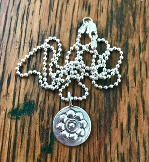 simple silver circular flower pendant on a silver beaded chain