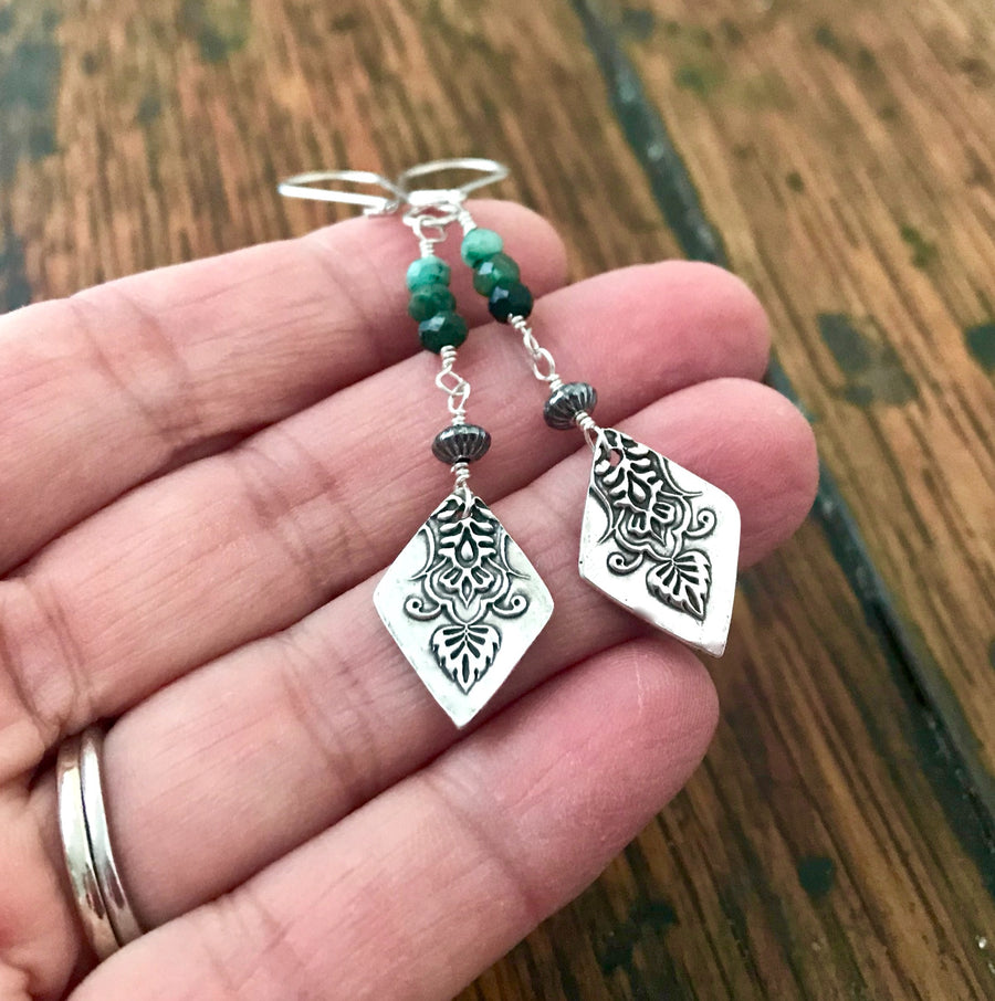 long,thin dangle earrings with small green emerald links and diamond shaped silver leaf drops