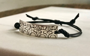 adjustable black leather cord bracelet with silver bar embossed with people standing united on it