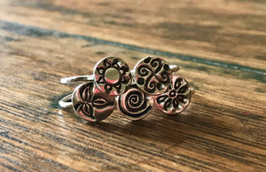 small circular silver sun, wind, flower, swirl, leaf emblems on silver rings