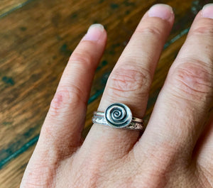 Circular silver swirl on thin silver ring band