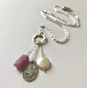 hammered silver ring on a chain with pink ruby, silver teardrop and white pearl charms