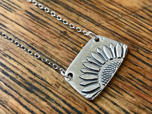silver embossed sunflower pendant on a textured silver chain