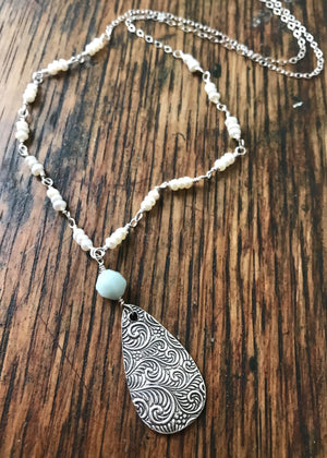 silver teardrop pendant with a swirl wind pattern with an amazonite bead on white pearl links and silver chain