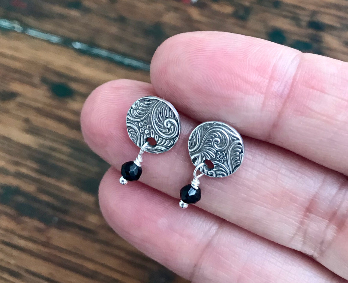 small circle shaped silver post earrings with a swirl and flower design and black spinel gemstone drops